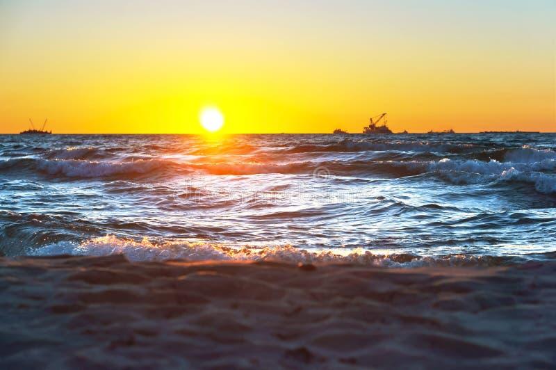 Κόκκινο κίτρινο ηλιοβασίλεμα στη θάλασσα, την ακτή στην κυματωγή των κυμάτων της θάλασσας της Βαλτικής και μια θαυμάσια ανατολή στοκ φωτογραφία με δικαίωμα ελεύθερης χρήσης