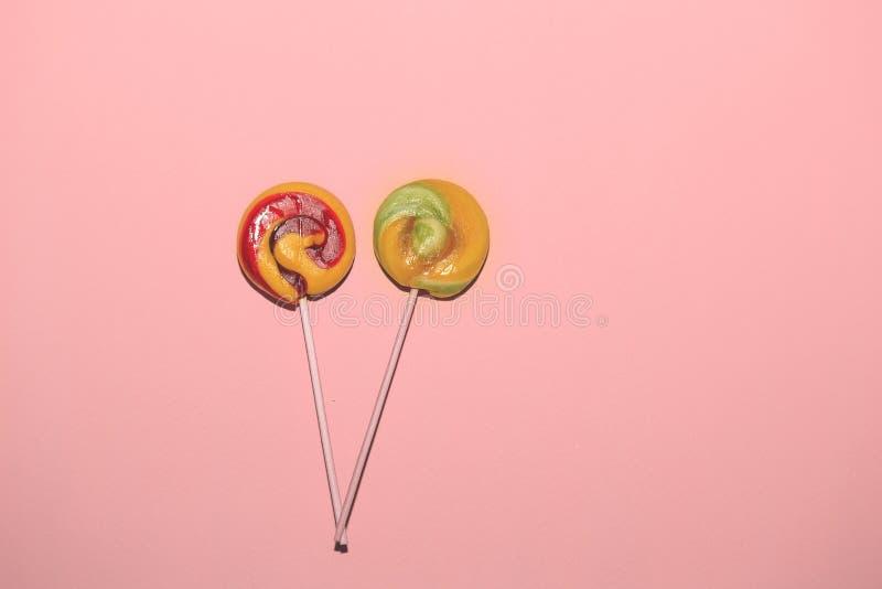 Κόκκινο, κίτρινο χρώμα lollipops στο ρόδινο υπόβαθρο εγγράφου στοκ φωτογραφίες
