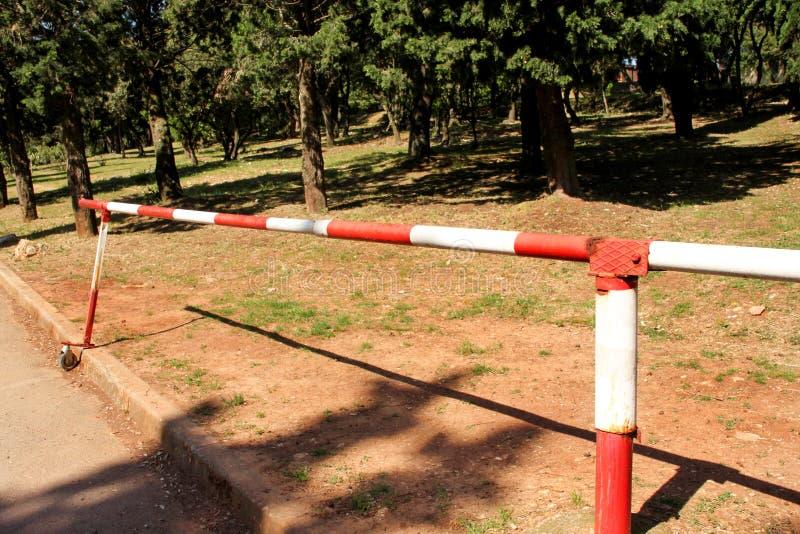 Κόκκινο και άσπρο εμπόδιο προειδοποιητικών σημαδιών στην πράσινη χλόη στο υπόβαθρο φύσης Μεταφορά, κανονισμός κυκλοφορίας στοκ εικόνα με δικαίωμα ελεύθερης χρήσης