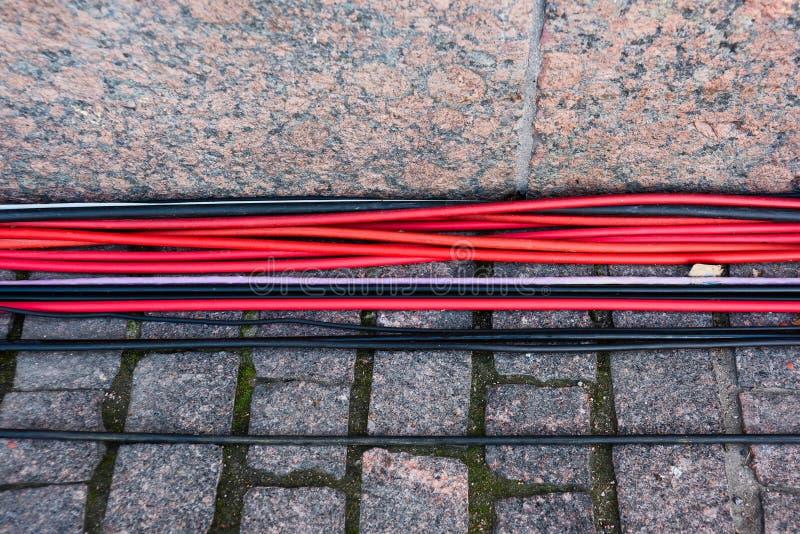 Κόκκινο και μαύρο καλώδιο στις πέτρες επίστρωσης στοκ εικόνα