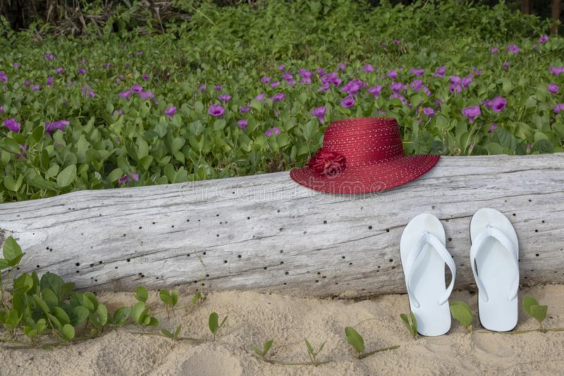Κόκκινο καπέλο αχύρου με τα άσπρα σανδάλια στο υπόβαθρο δόξας παραλιών άμμου και πρωινού παραλιών στοκ φωτογραφία με δικαίωμα ελεύθερης χρήσης