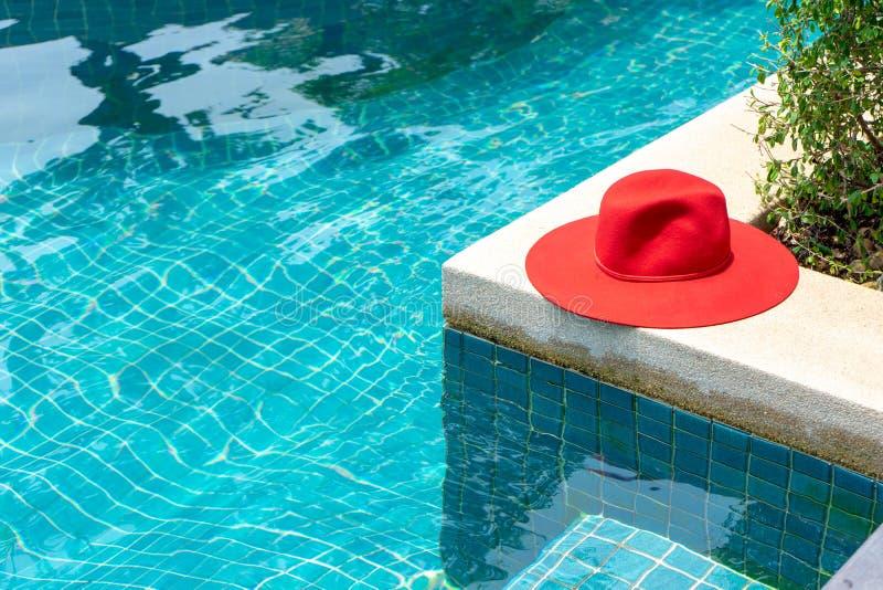 Κόκκινο καπέλο στην μπλε πισίνα νερού στοκ φωτογραφίες
