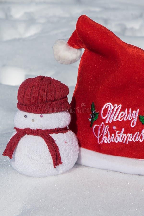 Κόκκινο καπέλο Χριστουγέννων και ένα καλό παιχνίδι χιονανθρώπων στο άσπρο χιόνι, στοκ εικόνες με δικαίωμα ελεύθερης χρήσης