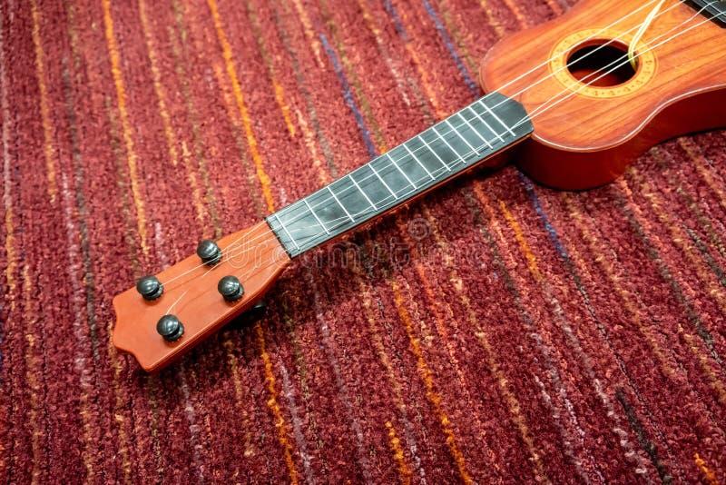 Κόκκινο καφετί πλαστικό ukulele με τις σπασμένες σειρές στο floo κόκκινου χαλιού στοκ εικόνες με δικαίωμα ελεύθερης χρήσης