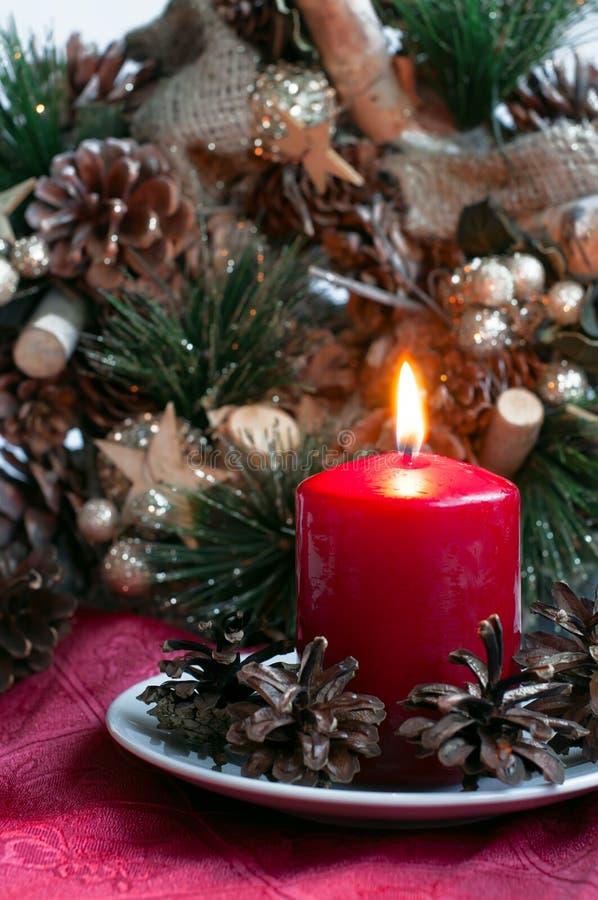 Κόκκινο κερί με τους κώνους έλατου και το στεφάνι Χριστουγέννων στοκ εικόνα με δικαίωμα ελεύθερης χρήσης