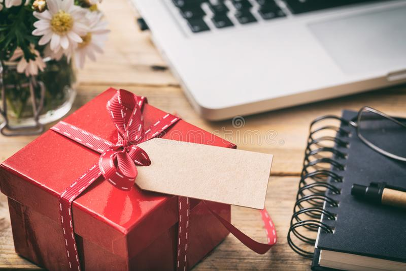 Κόκκινο κιβώτιο δώρων με την κενή κενή ετικέττα, υπόβαθρο γραφείων γραφείων θαμπάδων στοκ φωτογραφία με δικαίωμα ελεύθερης χρήσης