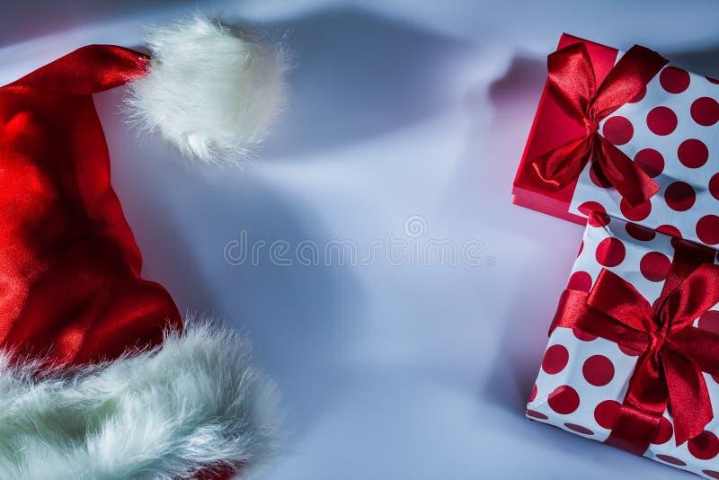 Κόκκινο κιβώτιο δώρων Santa συσκευασμένο καπέλο στο άσπρο υπόβαθρο στοκ φωτογραφία