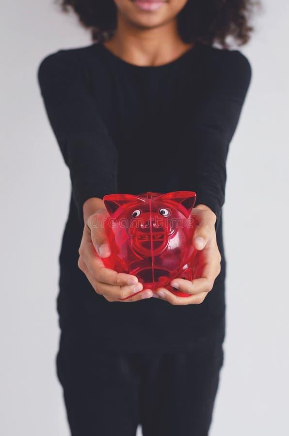 Κόκκινο κιβώτιο χρημάτων χοίρων στα χέρια ενός σκοτεινός-ξεφλουδισμένου κοριτσιού στοκ φωτογραφία
