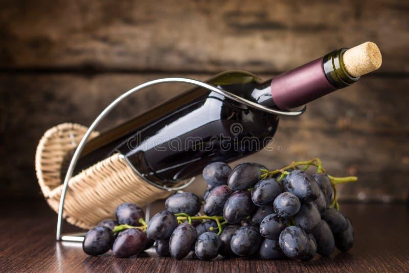 Κόκκινο κρασί με τη συστάδα των σκούρο μπλε σταφυλιών στον ξύλινο πίνακα στοκ φωτογραφίες