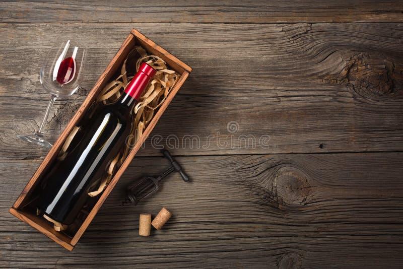 Κόκκινο κρασί σε ένα κιβώτιο με ένα γυαλί και ένα ανοιχτήρι σε έναν ξύλινο πίνακα Τοπ άποψη με το διάστημα για τους χαιρετισμούς  στοκ φωτογραφία με δικαίωμα ελεύθερης χρήσης