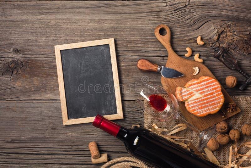 Κόκκινο κρασί σε ένα κιβώτιο με ένα τυρί γυαλιού, ανοιχτήρι και κρέμας σε έναν ξύλινο παλαιό πίνακα στοκ εικόνα