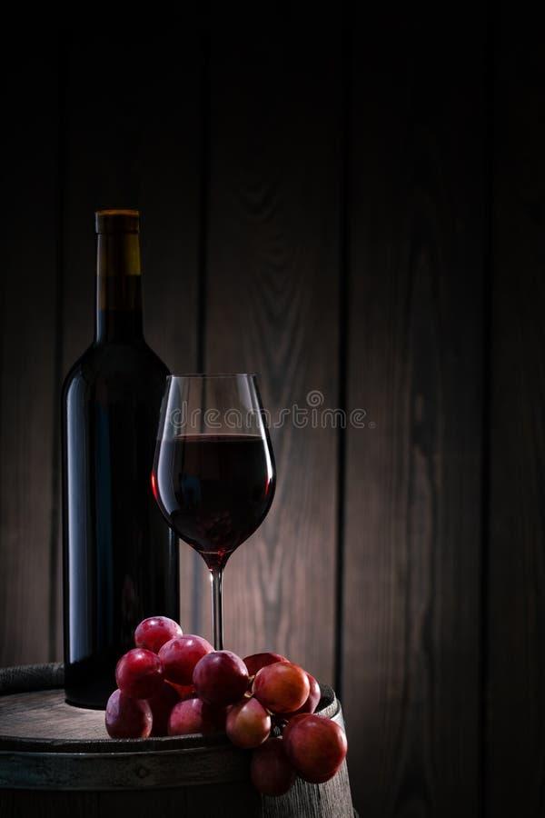Κόκκινο κρασί στο γυαλί και μπουκάλι που στέκεται στο βαρέλι με τη δέσμη των σταφυλιών στοκ εικόνα