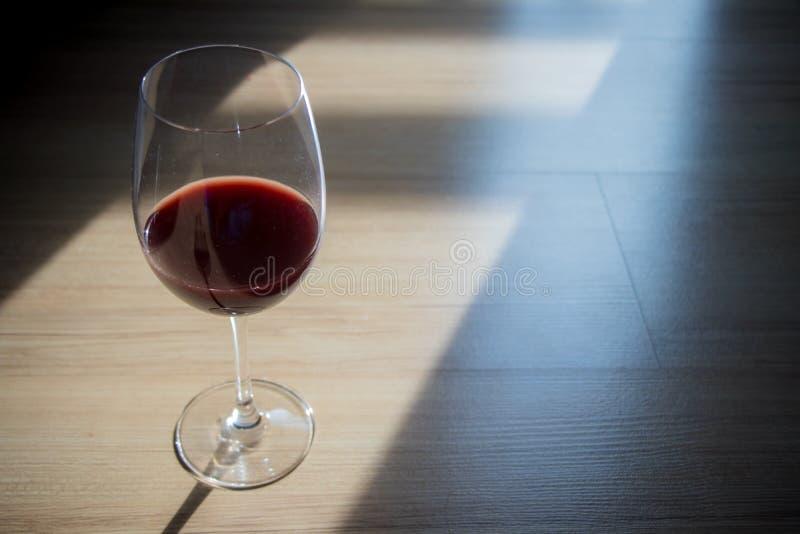 Κόκκινο κρασί στο γυαλί κρασιού, που τοποθετείται στο πάτωμα με το φως και τη σκιά παραθύρων στοκ εικόνες