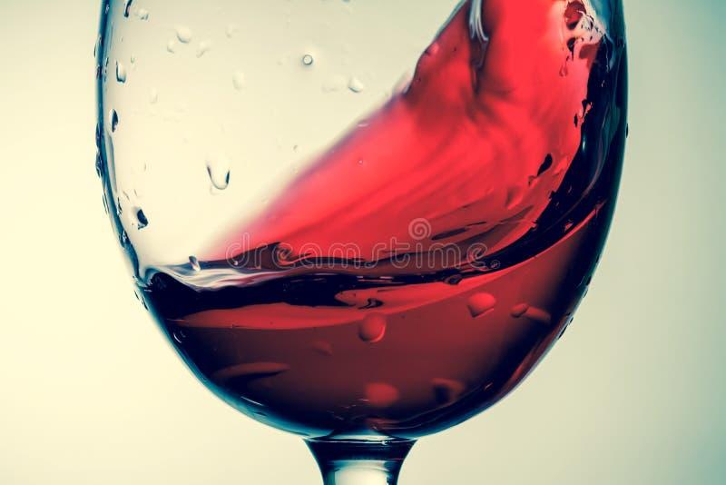 Κόκκινο κρασί στο γυαλί, ράντισμα, παφλασμός, κύμα του κόκκινου κρασιού κοντά επάνω στοκ εικόνα