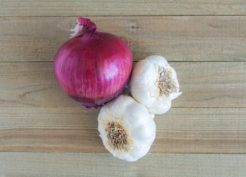 Κόκκινο κρεμμύδι και 2 βολβοί σκόρδου σε ένα ξύλινο υπόβαθρο στοκ εικόνες με δικαίωμα ελεύθερης χρήσης