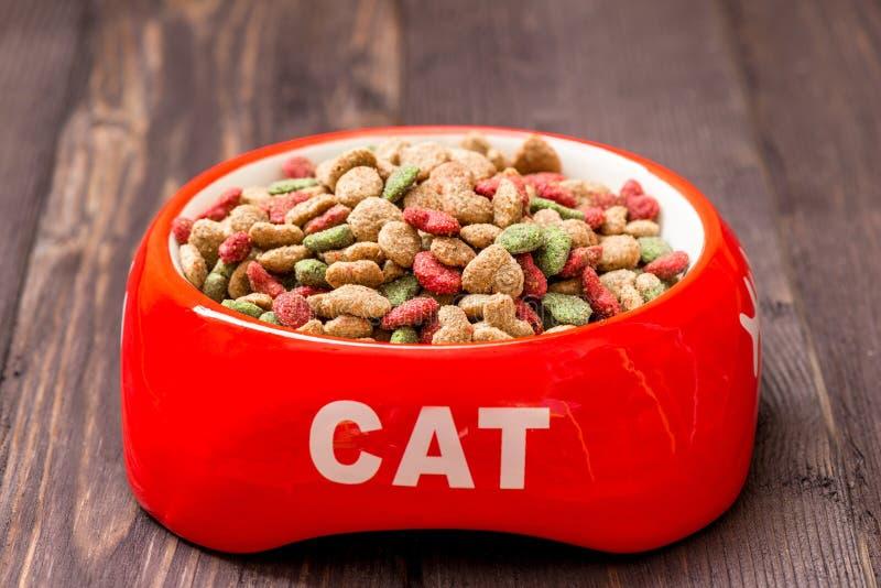 κόκκινο κύπελλο γατών κινηματογραφήσεων σε πρώτο πλάνο με τα ξηρά τρόφιμα στοκ φωτογραφία με δικαίωμα ελεύθερης χρήσης