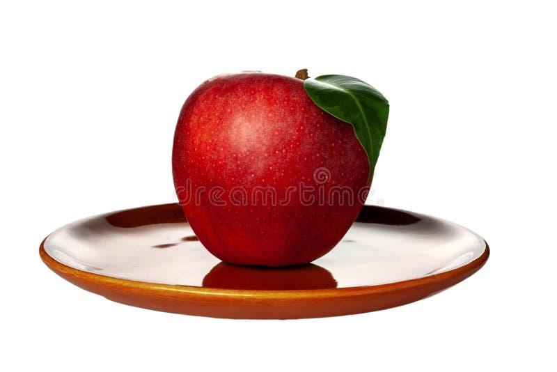 Κόκκινο μήλο που βρίσκεται σε ένα πιάτο αργίλου Στάσεις πιάτων σε ένα άσπρο υπόβαθρο απομονώστε στοκ εικόνες