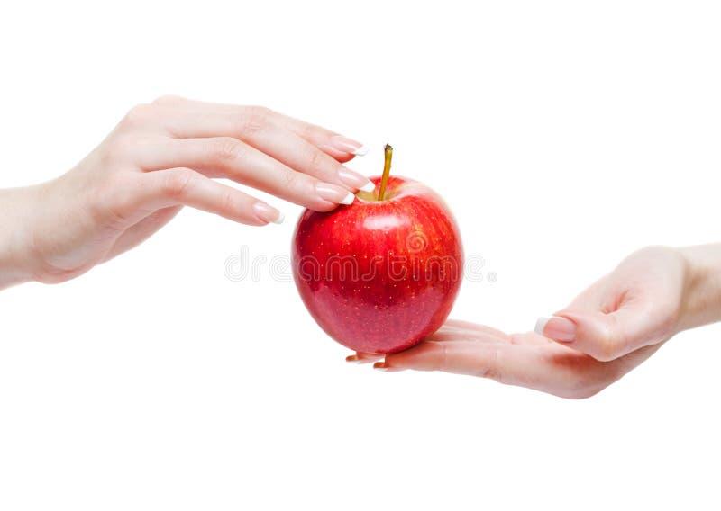 Κόκκινο μήλο μεταξύ των χεριών γυναικών στοκ φωτογραφίες