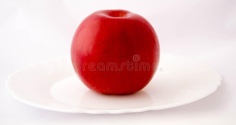 Κόκκινο μήλο σε ένα άσπρο πιάτο στοκ εικόνες
