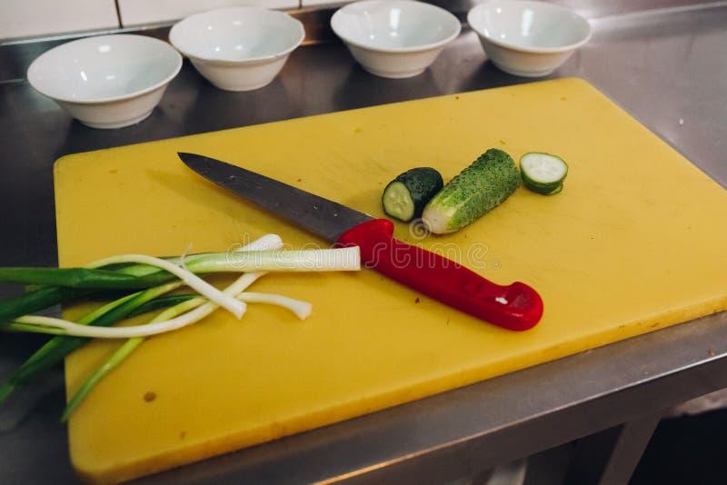 Κόκκινο μαχαίρι που βάζει κοντά στα φρέσκα πράσινα αγγούρια και το σκόρδο στον τεμαχισμό του πίνακα στοκ φωτογραφίες