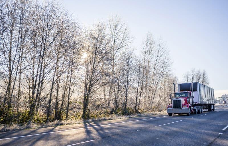 Κόκκινο μεγάλο αμερικανικό ημι φορτηγό αμαξιών ημέρας εγκαταστάσεων γεώτρησης που μεταφέρει το φορτίο στην καλυμμένη ημι οδήγηση  στοκ φωτογραφία με δικαίωμα ελεύθερης χρήσης
