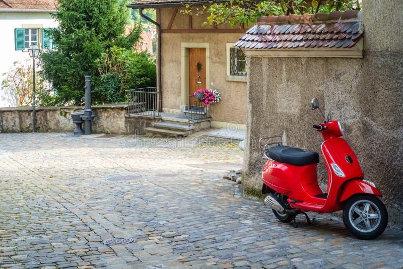 Κόκκινο μηχανικό δίκυκλο σε μια παλαιά γειτονιά σε Thun Ελβετία στοκ φωτογραφία με δικαίωμα ελεύθερης χρήσης