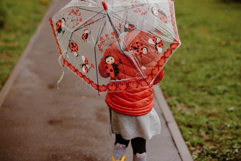 Κόκκινο μικρό παιδί κοριτσιών θερινών κίτρινο μποτών ομπρελών στοκ φωτογραφίες με δικαίωμα ελεύθερης χρήσης