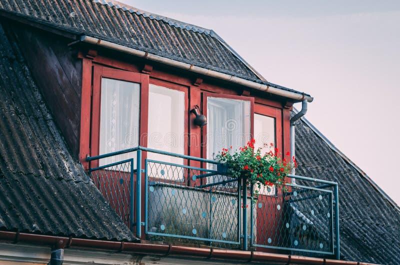 Κόκκινο μπαλκόνι στο παλαιό σπίτι κατά τη διάρκεια του ηλιοβασιλέματος στοκ εικόνα με δικαίωμα ελεύθερης χρήσης