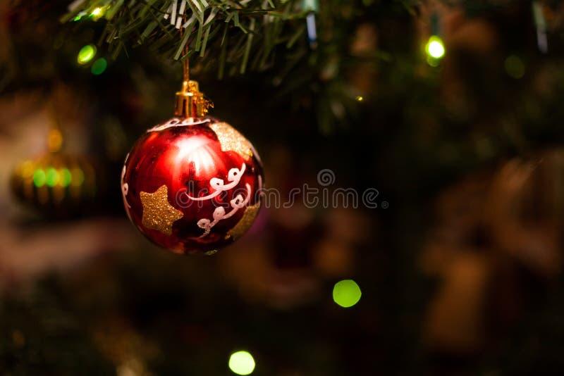 Κόκκινο μπιχλιμπίδι γυαλιού στο τεχνητό χριστουγεννιάτικο δέντρο στοκ εικόνες