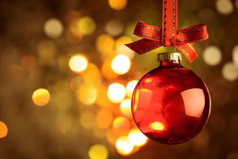 Κόκκινο μπιχλιμπίδι Χριστουγέννων πέρα από το μαγικό υπόβαθρο bokeh στοκ εικόνες