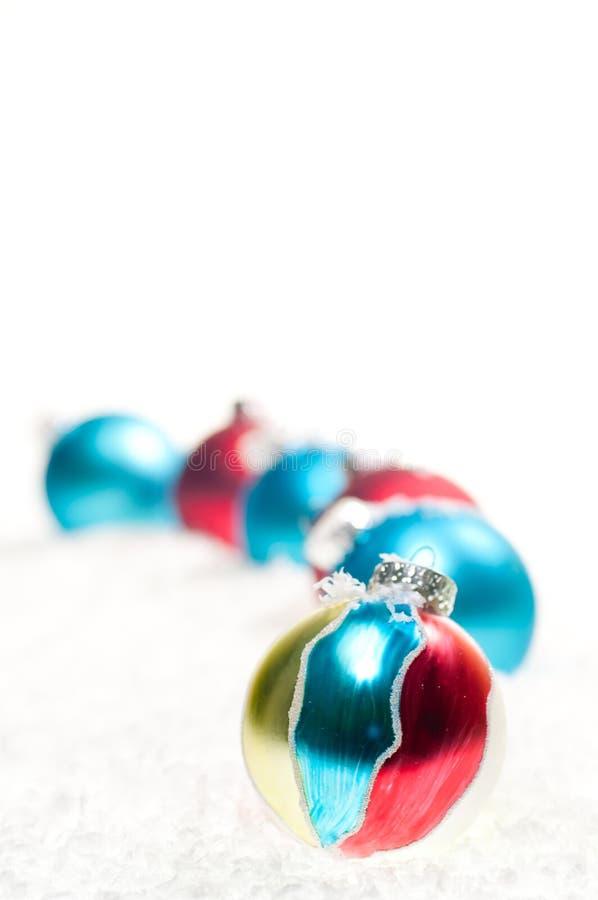 Κόκκινο, μπλε και χρυσό μπιχλιμπίδι Χριστουγέννων στο χιόνι στοκ φωτογραφία