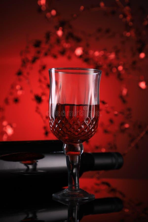 Κόκκινο μπουκάλι κρασιού και γυαλιά με εορταστική αίσθηση στοκ εικόνα