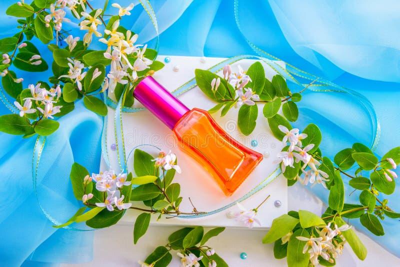 Κόκκινο μπουκάλι αρώματος γυαλιού και ρόδινα λουλούδια στοκ φωτογραφία με δικαίωμα ελεύθερης χρήσης