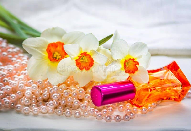 Κόκκινο μπουκάλι αρώματος γυαλιού, χάντρες μαργαριταριών και daffodil λουλούδια στοκ εικόνα