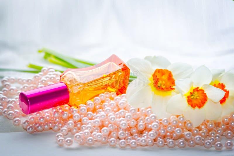 Κόκκινο μπουκάλι αρώματος γυαλιού, χάντρες μαργαριταριών και daffodil λουλούδια στοκ φωτογραφία με δικαίωμα ελεύθερης χρήσης