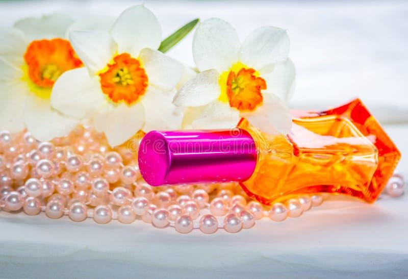 Κόκκινο μπουκάλι αρώματος γυαλιού, χάντρες μαργαριταριών και daffodil λουλούδια στοκ εικόνες