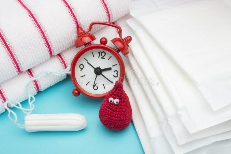 Κόκκινο ξυπνητήρι, ονειροπόλος πτώση αίματος τσιγγελακιών χαμόγελου, καθημερινό εμμηνορροϊκό μαξιλάρι και tampon και πετσέτα υφασ στοκ εικόνες