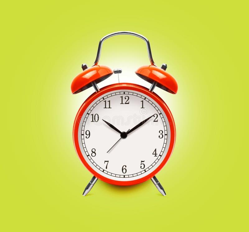 Κόκκινο ξυπνητήρι που απομονώνεται σε κίτρινο στοκ εικόνες