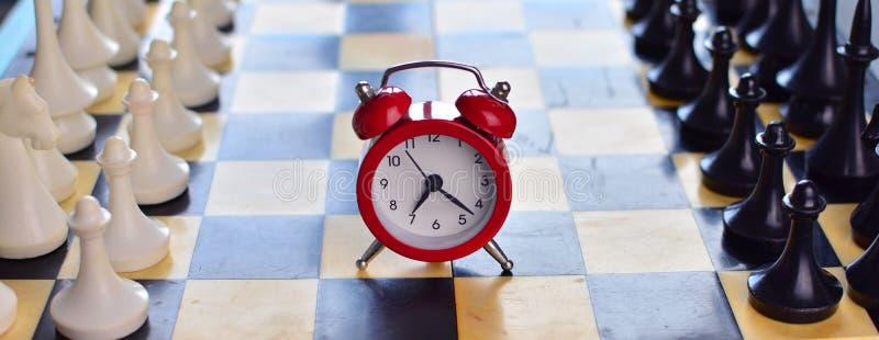 Κόκκινο ξυπνητήρι σε μια σκακιέρα με το σκάκι στοκ εικόνες