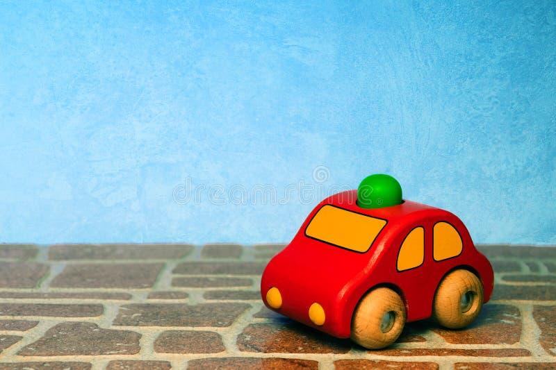 Κόκκινο ξύλινο αυτοκίνητο παιχνιδιών στο ζωηρόχρωμο υπόβαθρο στοκ εικόνες με δικαίωμα ελεύθερης χρήσης