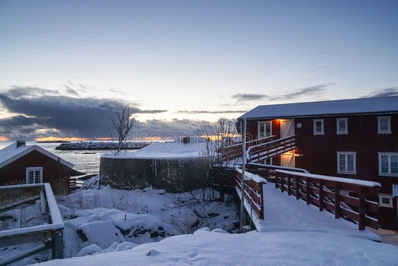 Κόκκινο ξύλινο σπίτι για τον ψαρά στο νησί Νορβηγία Lofoten που καλύπτεται με το παχύ άσπρο χιόνι το χειμώνα μετά από τις χιονοπτ στοκ φωτογραφίες
