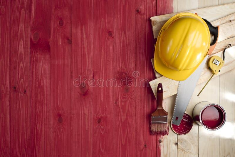 Κόκκινο ξύλινο πάτωμα με μια βούρτσα, ένα χρώμα, τα εργαλεία και το κράνος στοκ φωτογραφία με δικαίωμα ελεύθερης χρήσης