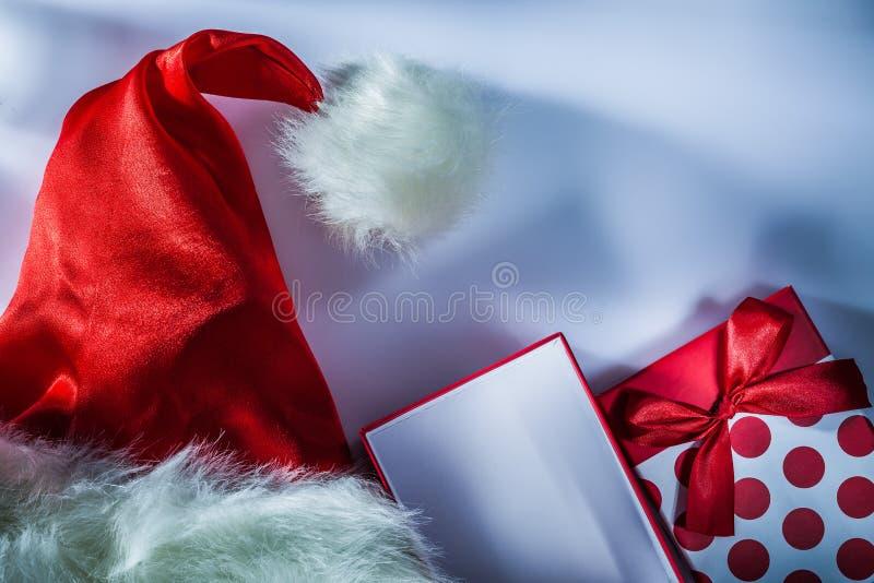 Κόκκινο παρόν κιβώτιο Άγιου Βασίλη ΚΑΠ στην άσπρη επιφάνεια στοκ εικόνα