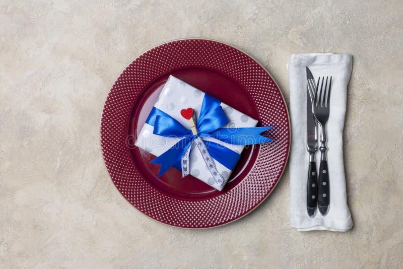 Κόκκινο πιάτο με το κιβώτιο δώρων, με το δίκρανο και το μαχαίρι στο άσπρο υπόβαθρο Ρομαντική ομοφυλοφιλική ένδυση πιάτων στοκ εικόνα