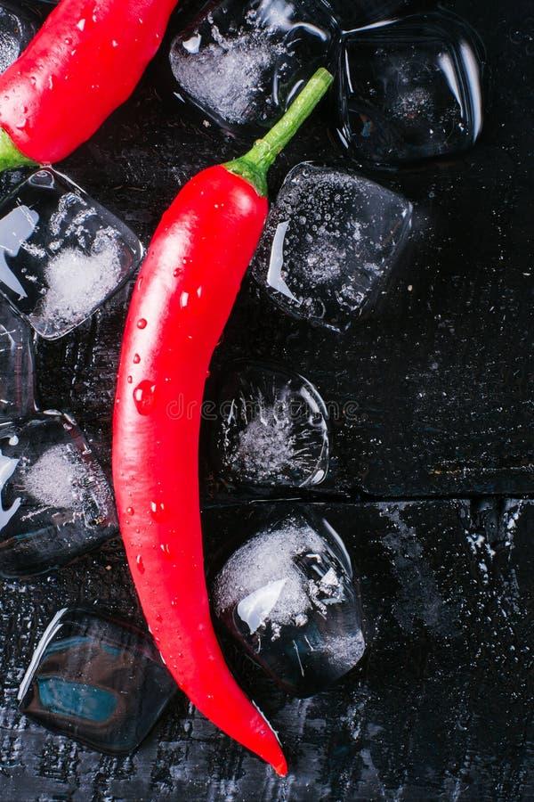 Κόκκινο πιπέρι και πάγος σε ένα μαύρο ξύλινο υπόβαθρο, φρέσκα καυτά τρόφιμα στον εκλεκτής ποιότητας πίνακα, κρύος πάγος κύβων παγ στοκ φωτογραφία με δικαίωμα ελεύθερης χρήσης
