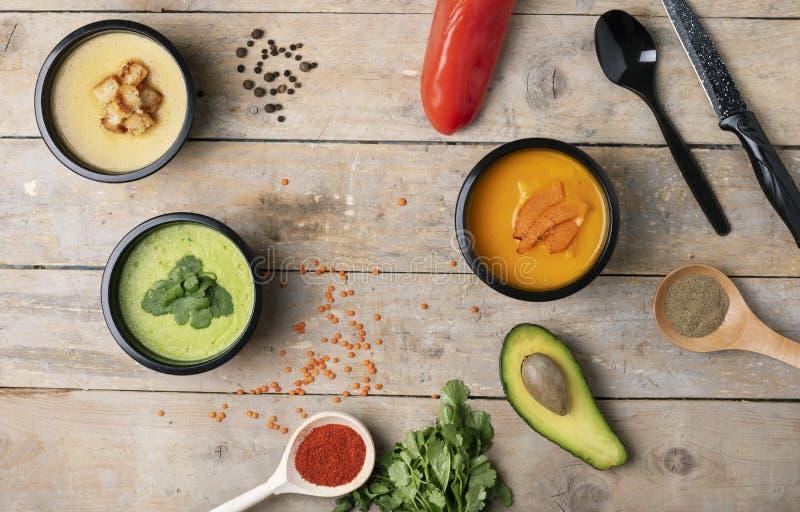Κόκκινο πιπέρι, μισά avacado και κουτάλι κοντά στις vegan σούπες στα εμπορευματοκιβώτια τροφίμων, έτοιμο γεύμα που τρώει στοκ φωτογραφία