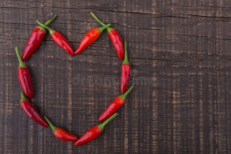 Κόκκινο πιπέρι πάπρικας με μορφή της καρδιάς. Η σύσταση σε ένα ξύλινο υπόβαθρο. Ημέρα βαλεντίνου. στοκ φωτογραφίες με δικαίωμα ελεύθερης χρήσης