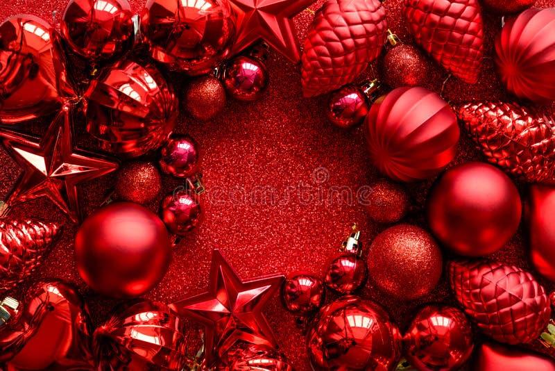 κόκκινο πλαισίων Χριστο&upsil Σφαίρες, αστέρια, κώνοι και καρδιές Χριστουγέννων στο κόκκινο υπόβαθρο σπινθηρισμάτων Επίπεδος βάλτ στοκ εικόνα