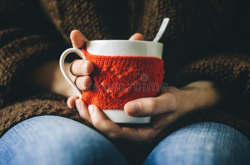 Κόκκινο πλεκτό μάλλινο φλυτζάνι με το σχέδιο καρδιών στα θηλυκά χέρια στοκ εικόνες