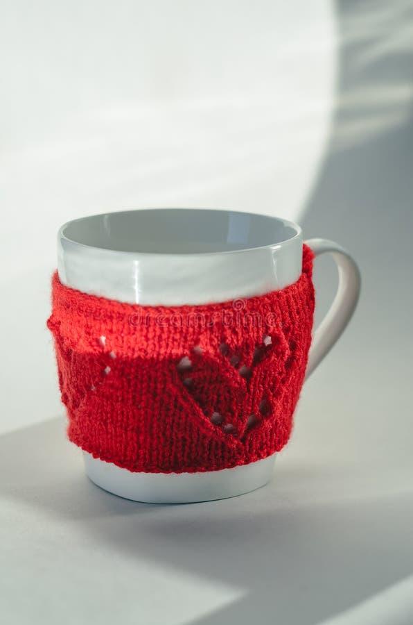 Κόκκινο πλεκτό μάλλινο φλυτζάνι με το σχέδιο καρδιών στοκ εικόνες